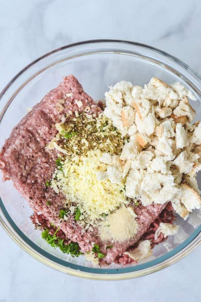 pork mince, bread and other ingredients in a glass bowl