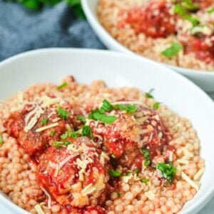 a white bowl containing meatballs, cous cous and herbs