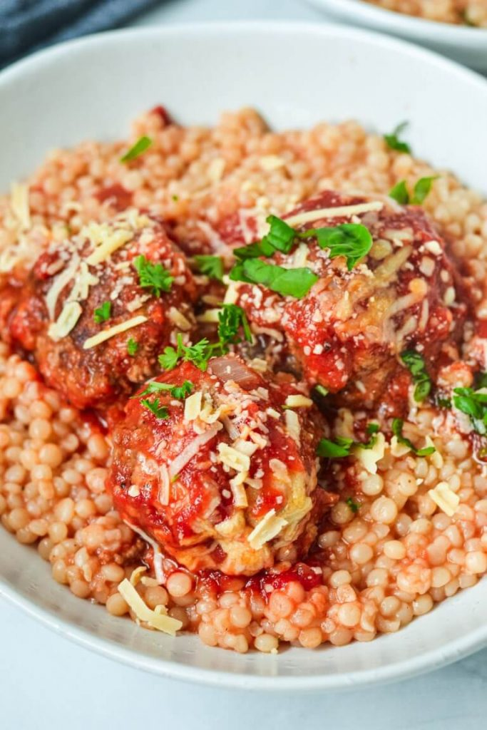 A close up of a plate of baked meatballs over cous cous with herbs