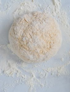 top view of pizza dough on floured bench