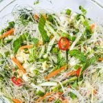noodles and fresh herbs in glass bowl