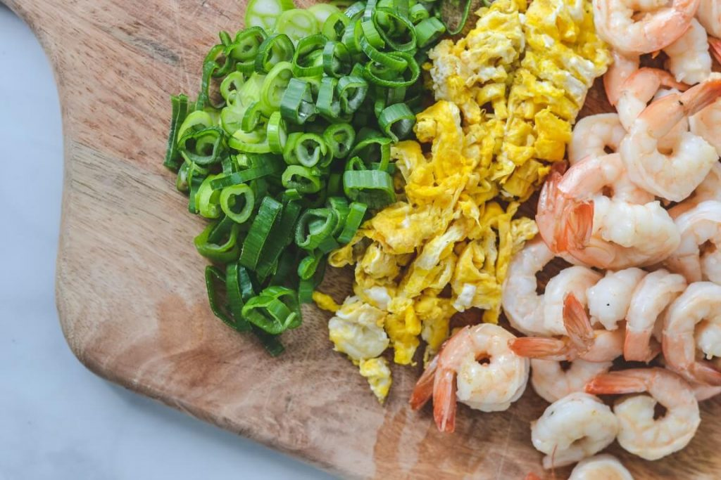 chopped spring onion, egg and prawns on wooden board