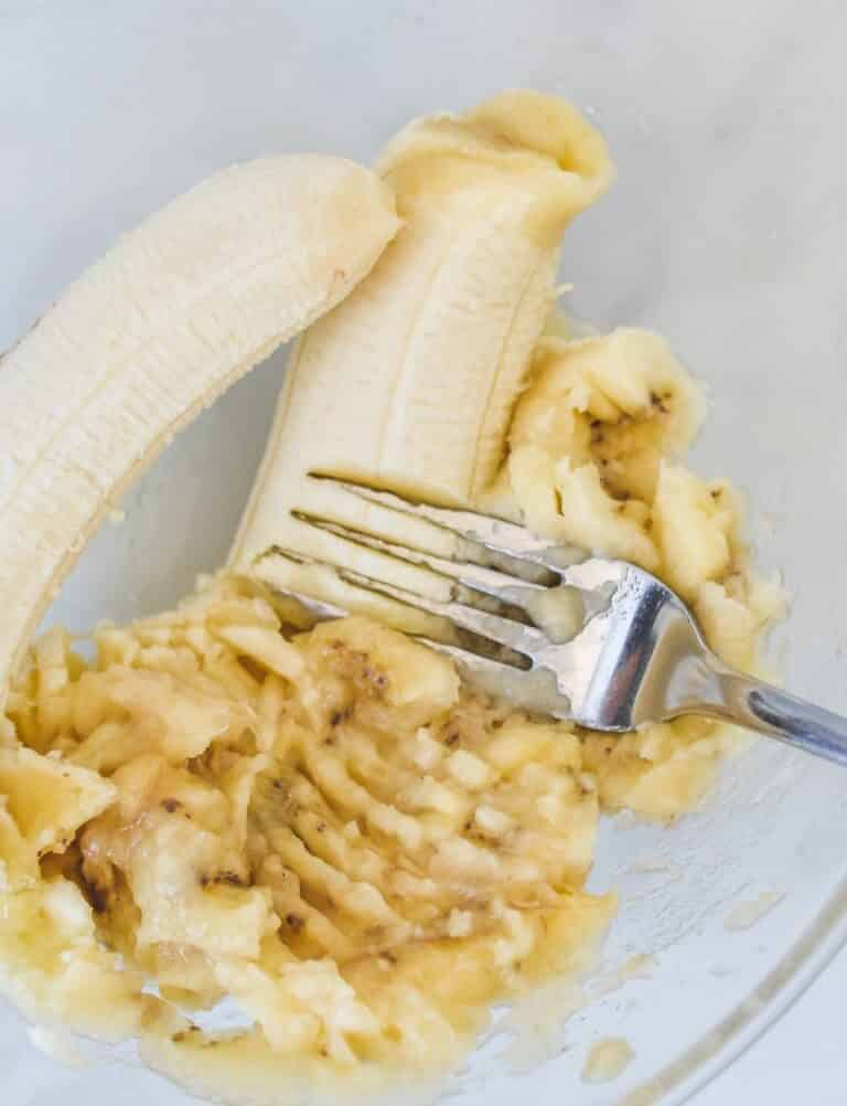 top view of a fork, mashing a banana