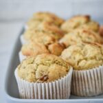 banana muffins in white paper cases on a blue platter