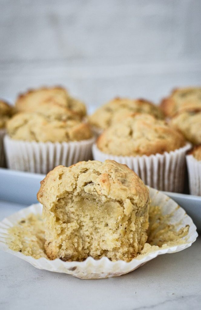 close up of a muffin in a paper case with a bite taken from the front