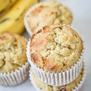 A close up of banana muffins in paper cases with banana in background