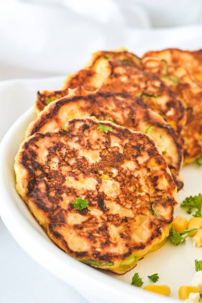 corn fritters arranged in white bowl with parsley