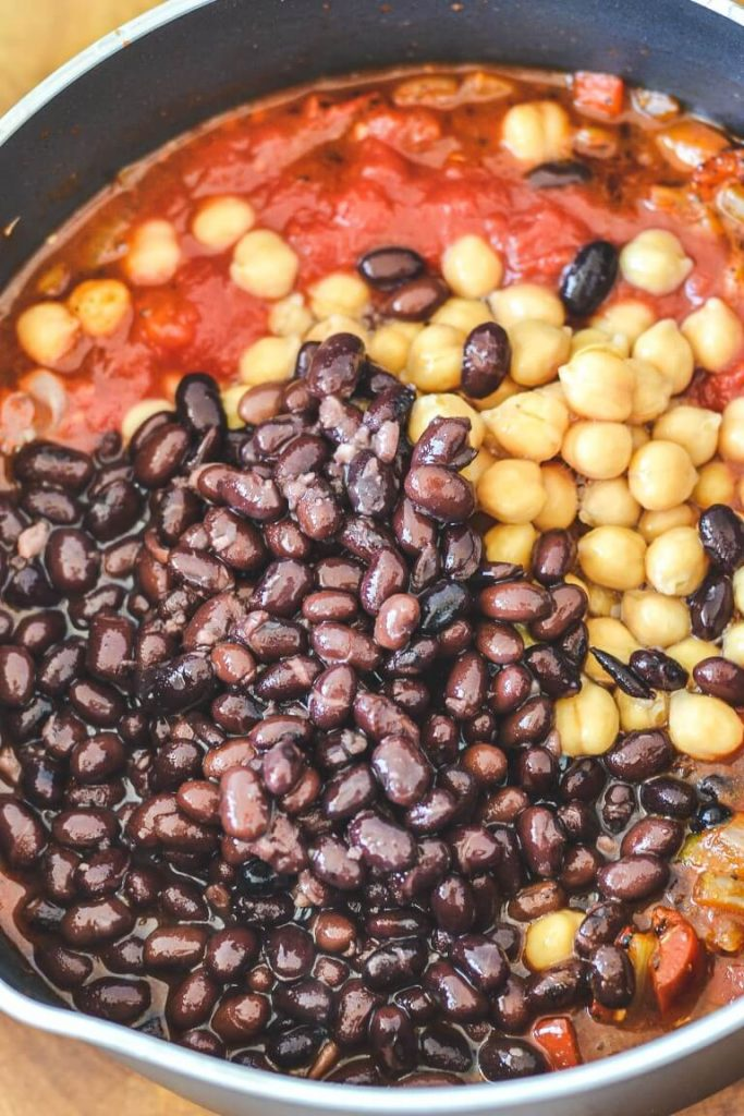 black beans, chickpeas and tomatoes in black pan