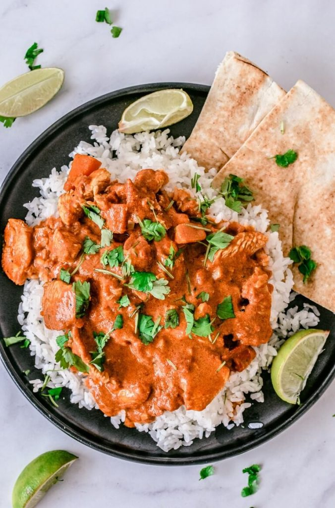 tikka-masala-with-vegetables-and-rice-on-black-plate