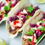 top view of colourful pork tacos with cabbage and coriander