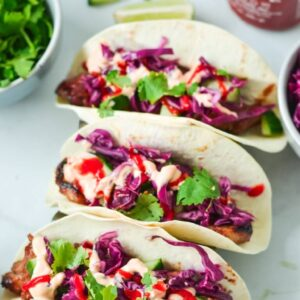 tacos on white bench, filled with pork, cabbage and sriracha