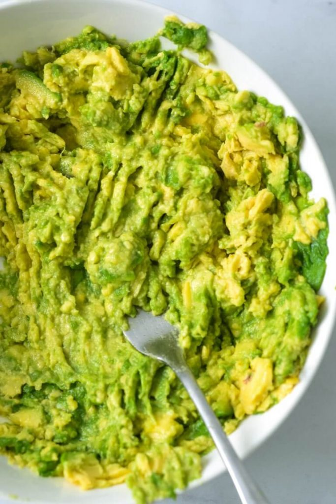 top view of mashed avocado in white bowl with a fork