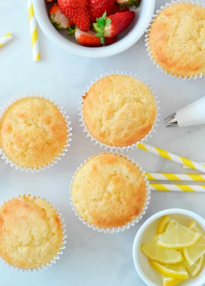 cupcakes-on-white-bench-with-piping-bag-and-lemon-wedges