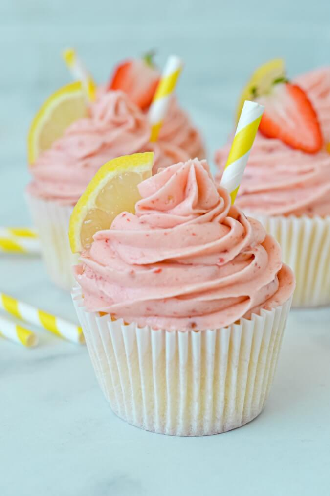 close up of cupcake in paper case with pink icing, wedge of lemon and a straw