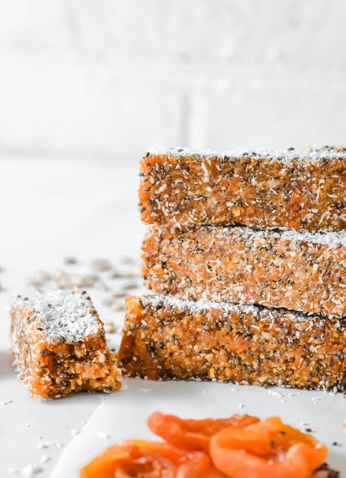 stacked apricot bars covered in coconut on white bench