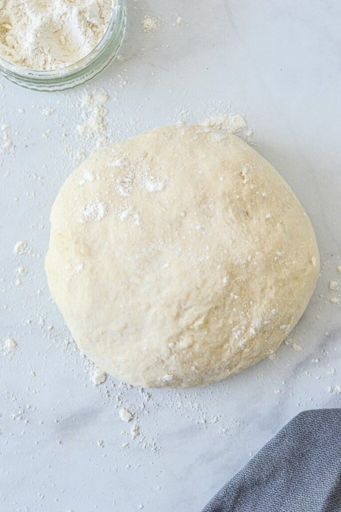 top view of pizza dough with sprinkled flour on white table