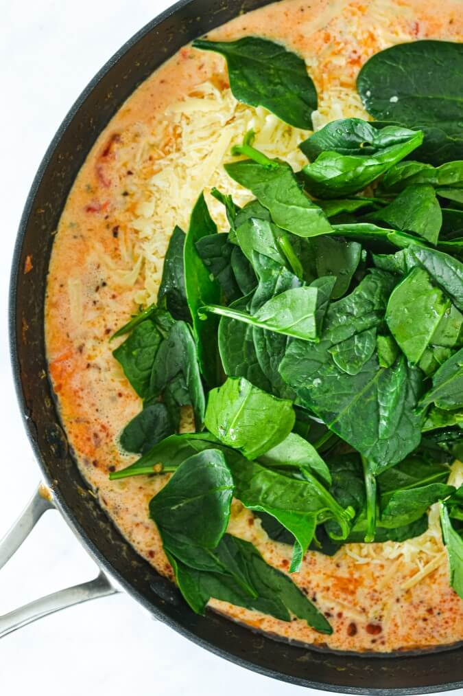 top view of spinach leaves in pan with cream pasta sauce