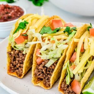 hard-shell-tacos-with-meat-and-salad-on-white-plate