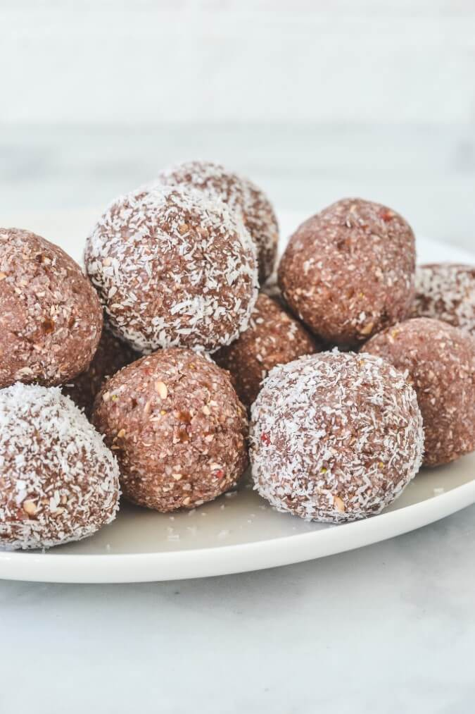 close up of bliss balls on a white plate