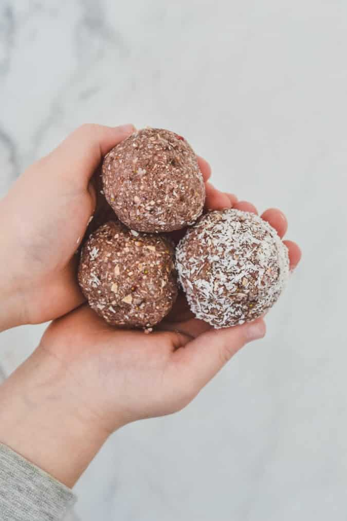 top view of two hands, holding three bliss balls