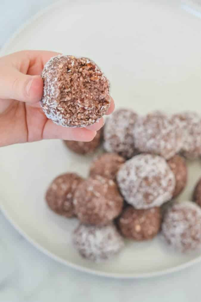 hand-holding-strawberry-bliss-ball-with-bite-mark