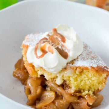 browned-apples-topped-with-sponge-pudding-and-cream-in-white-bowl