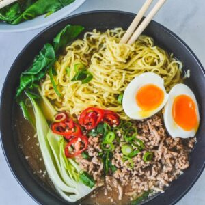 A bowl of soup with ramen noodles, eggs and pork mince