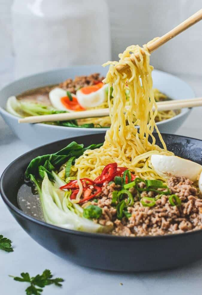 noodles-held-by-chopsticks-above-bowl-of-soup