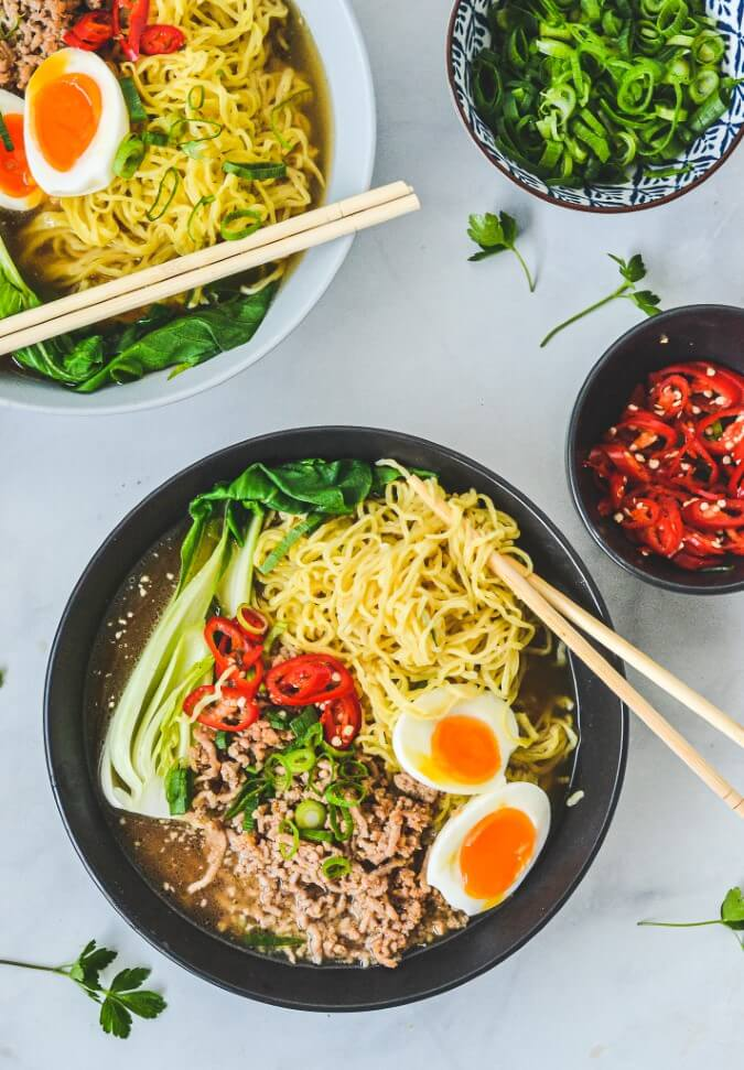 top-view-of-pork-mince-ramen-and-garnishes-in-bowls