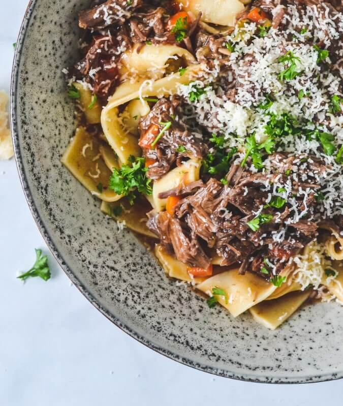 top view of meat sauce over pasta in grey bowl
