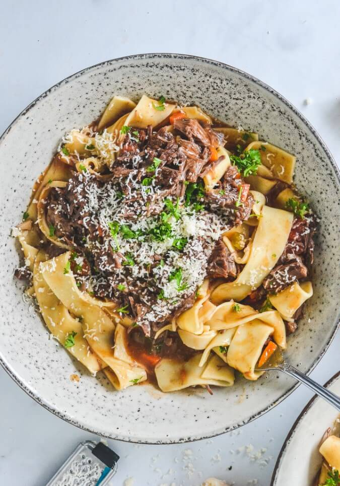 top view of meat ragu sauce with pasta in grey bowl