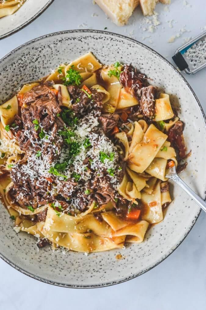 beef-ragu-sauce-spooned-over-cooked-pasta-in-grey-bowl