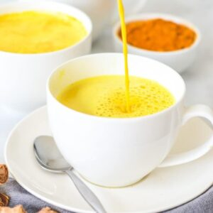 yellow-latte-being-poured-into-white-cup