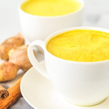 yellow turmeric latte in white cups beside ginger and cinnamon sticks