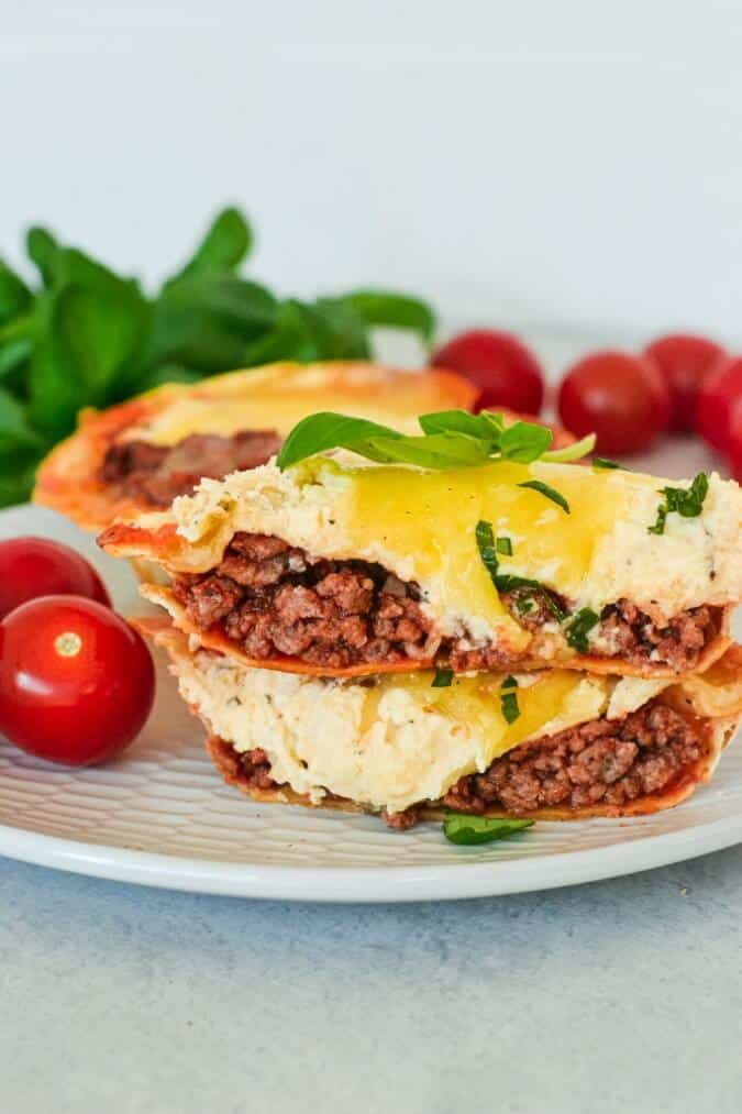 sliced-lasagne-on-white-plate-with-cherry-tomatoes