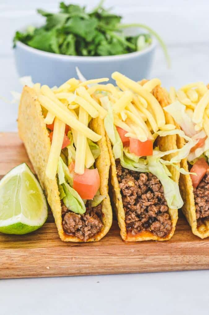 ground-taco-meat-in-crispy-shells-on-wooden-board-topped-with-cheese