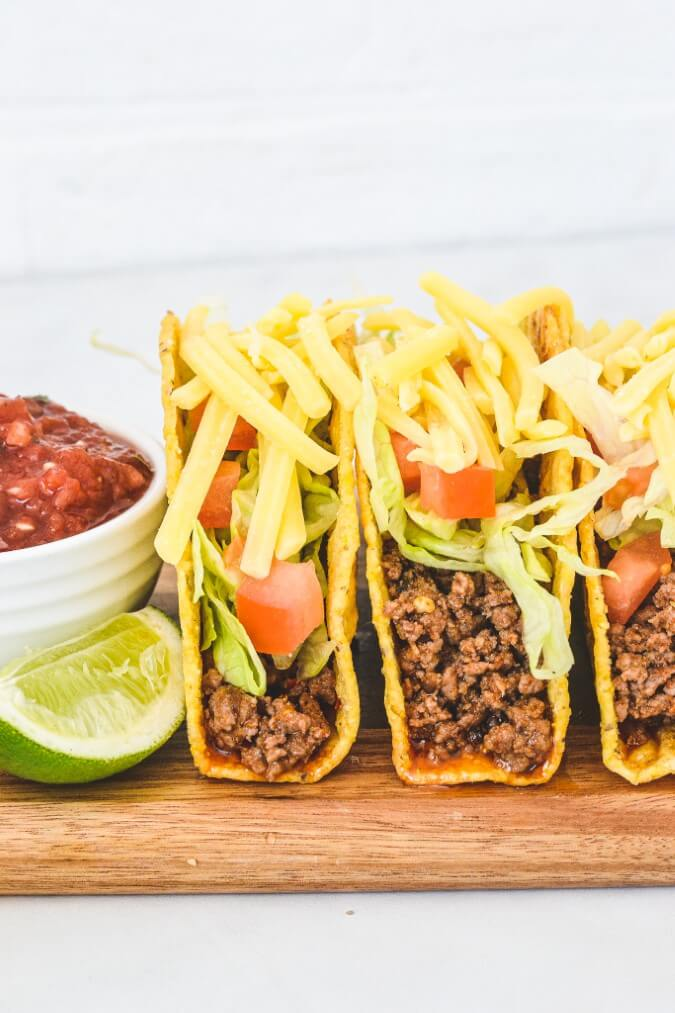 assembled tacos with hard shells on wooden board