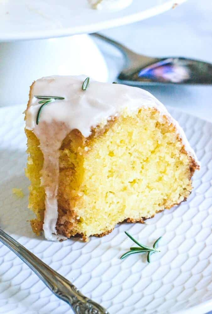 slice-of-finished-cake-with-white-icing-and-rosemary-on-white-plate