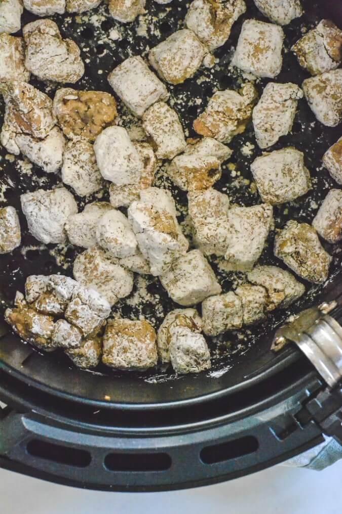 pieces of floured pork in air fryer basket