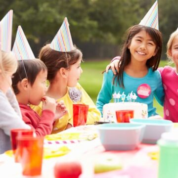 happy-children-with-party-hats-at-colourful-table