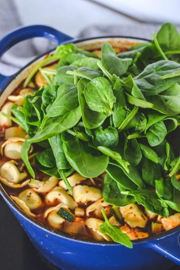 green spinach leaves and tortellini on top of soup in pot