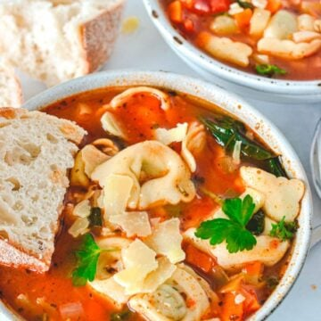 red-soup-in-grey-bowl-with-tortellini-and-bread-on-the-side