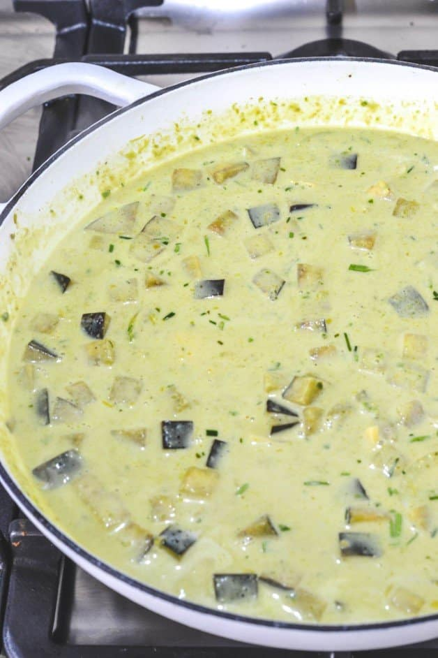 coconut-milk-added-to-curry-paste-in-white-pan