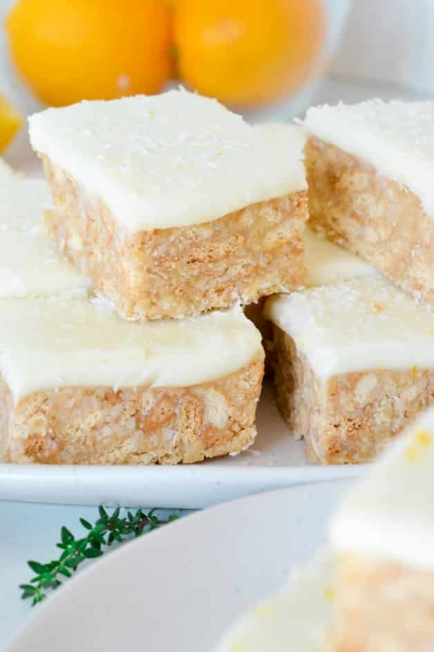 slice-with-white-icing-and-lemons-on-white-plate