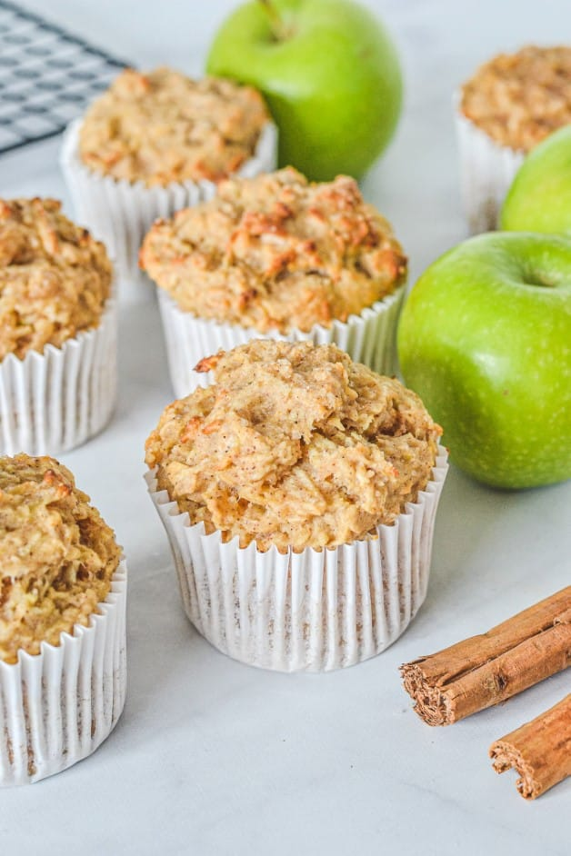 apple-muffins-in-paper-cases-on-white-board-with-cinnamon-sticks