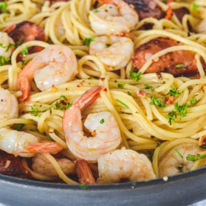 A frying pan filled with spaghetti, prawns and chorizo, sprinkled with herbs