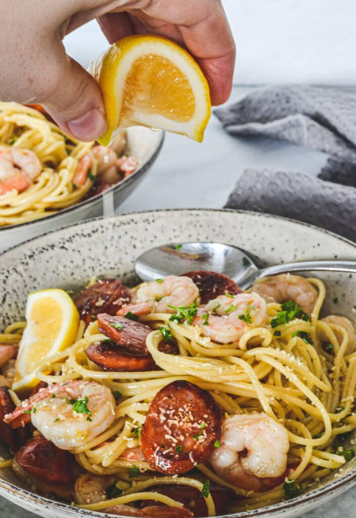 pasta-in-bowl-with-prawn-and-chorizo-hand-squeezing-lemon-juice