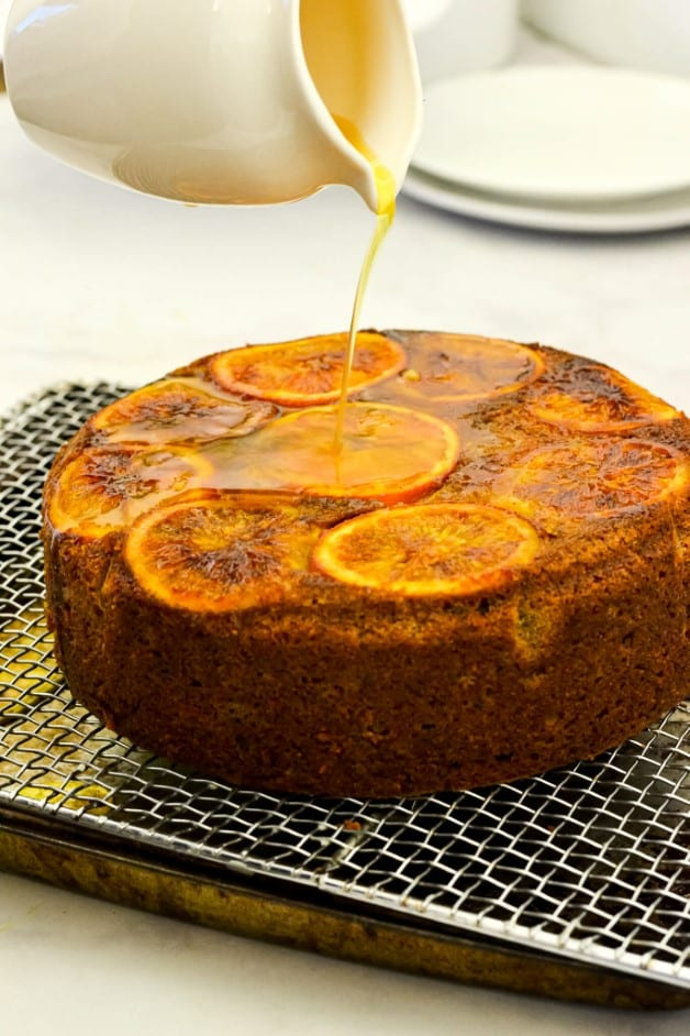 white jug pouring syrup over orange cake