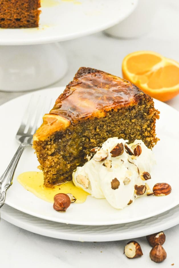slice of orange cake with hazelnut pieces and whipped cream