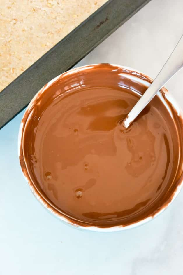melted chocolate in a glass bowl with a spoon